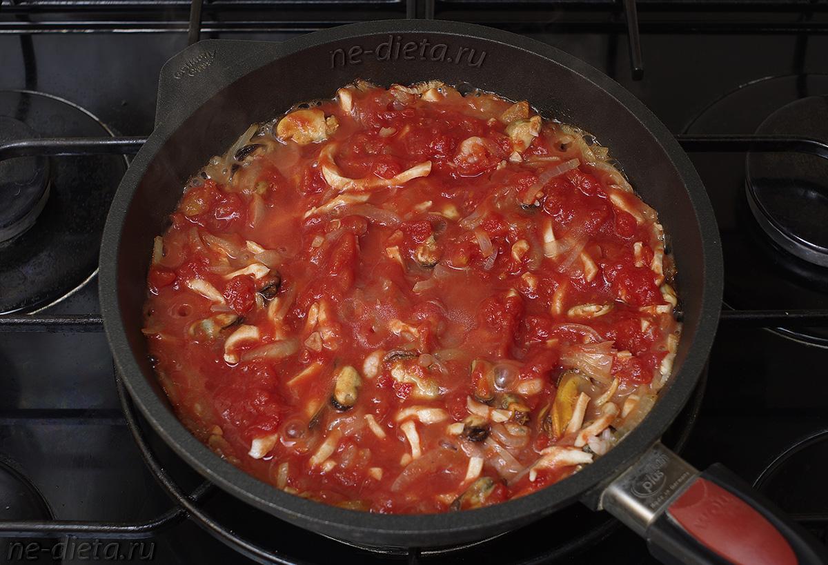 К морепродуктам добавить измельченные томаты