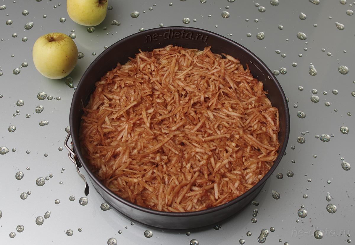 Яблоки натереть на терке и выложить на тесто
