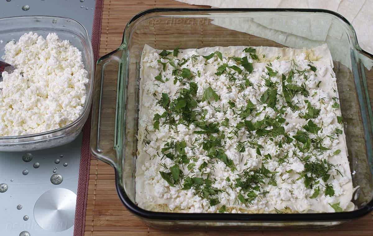 Положить второй лист лаваша и посыпать творогом и зеленью