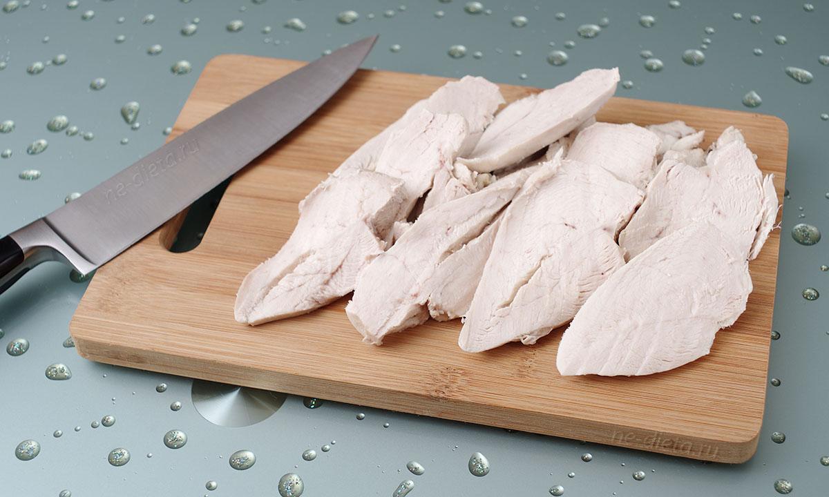 Отварное куриное филе нарезать порционными ломтиками