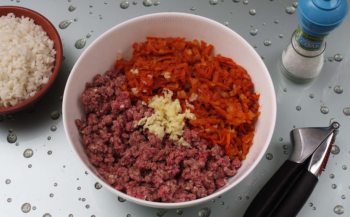В миску выложить мясной фарш, овощную зажарку, рис и измельченный чеснок
