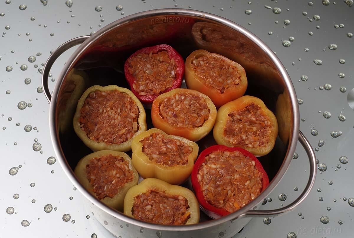 Болгарские перцы заполнить мясным фаршем и поставить вертикально в кастрюлю