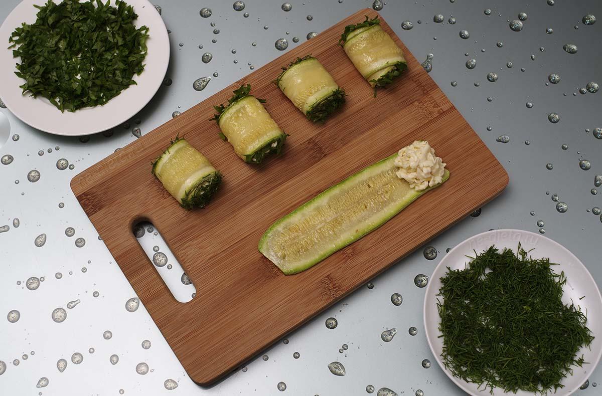 На кабачок положить сыр, свернуть рулетик и обмакнуть его с боков в зелень