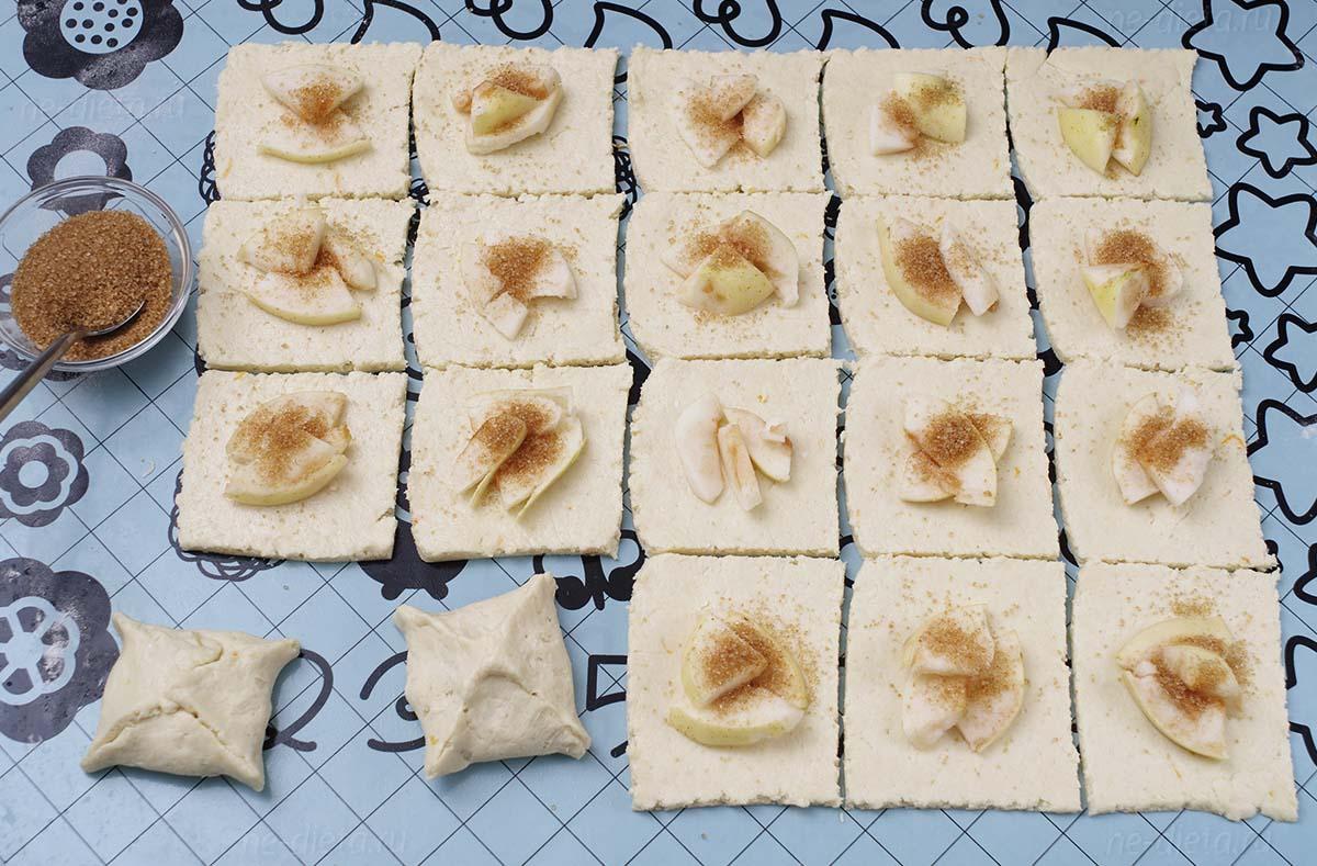 На тесто выложить яблоки и посыпать сахаром