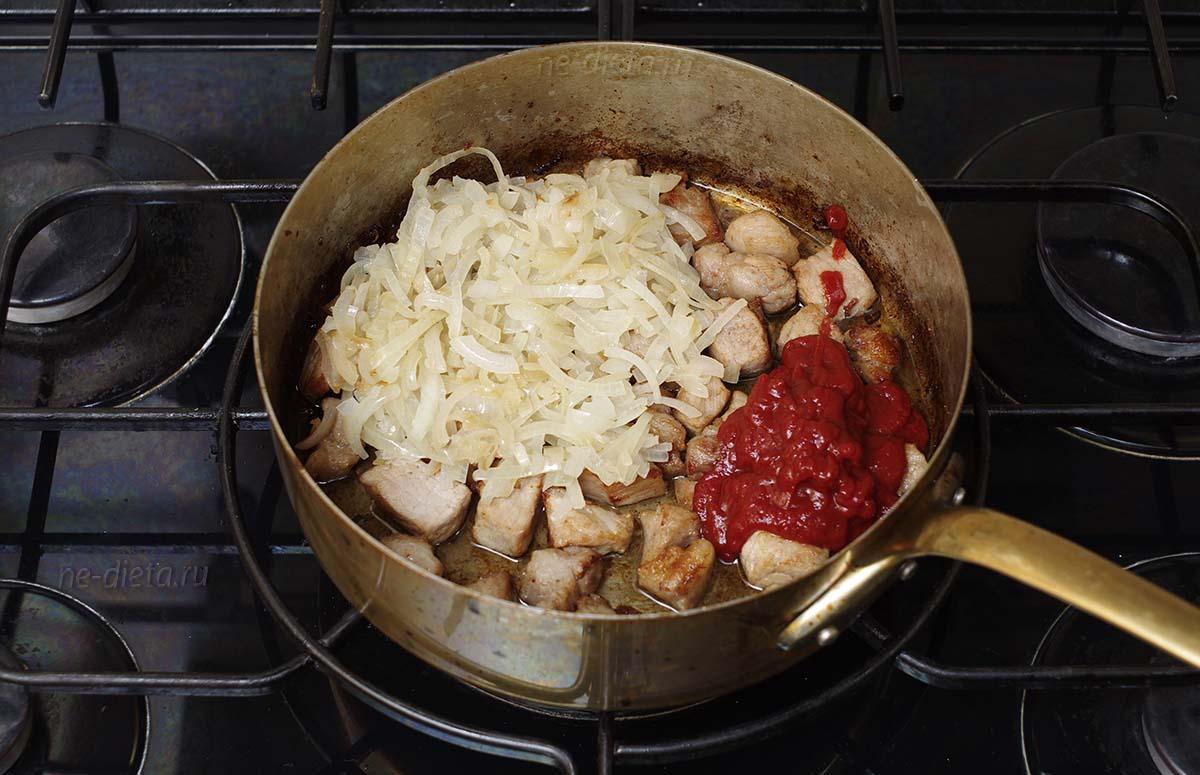 К мясу добавить лук и томатную пасту