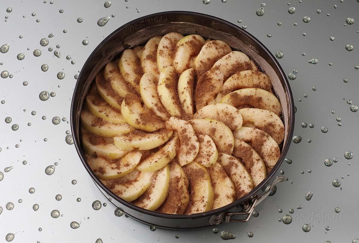 На тесто веером выложить яблоки и посыпать их сахаром и корицей