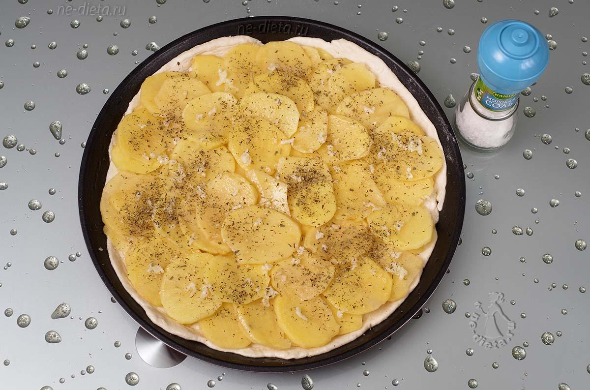 На тесто выложить картофель и чеснок