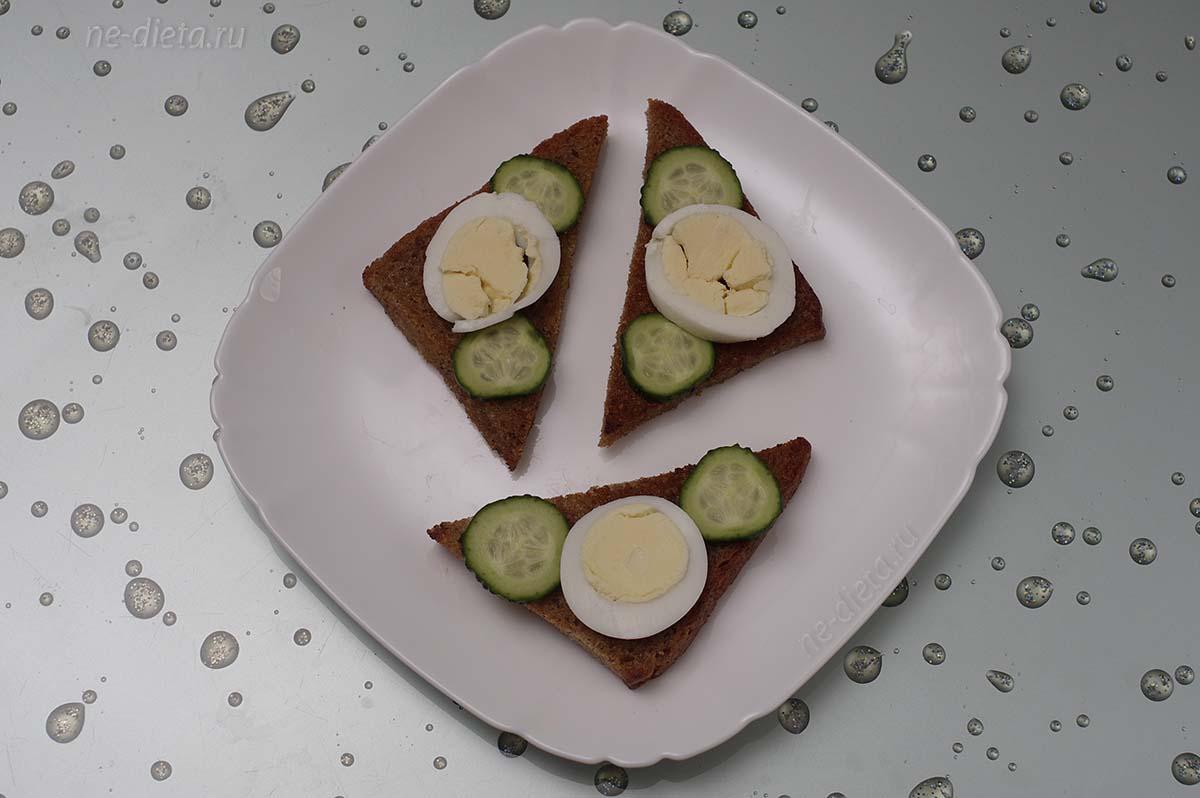 На ломтики хлеба выложить кружки яйца и огурца
