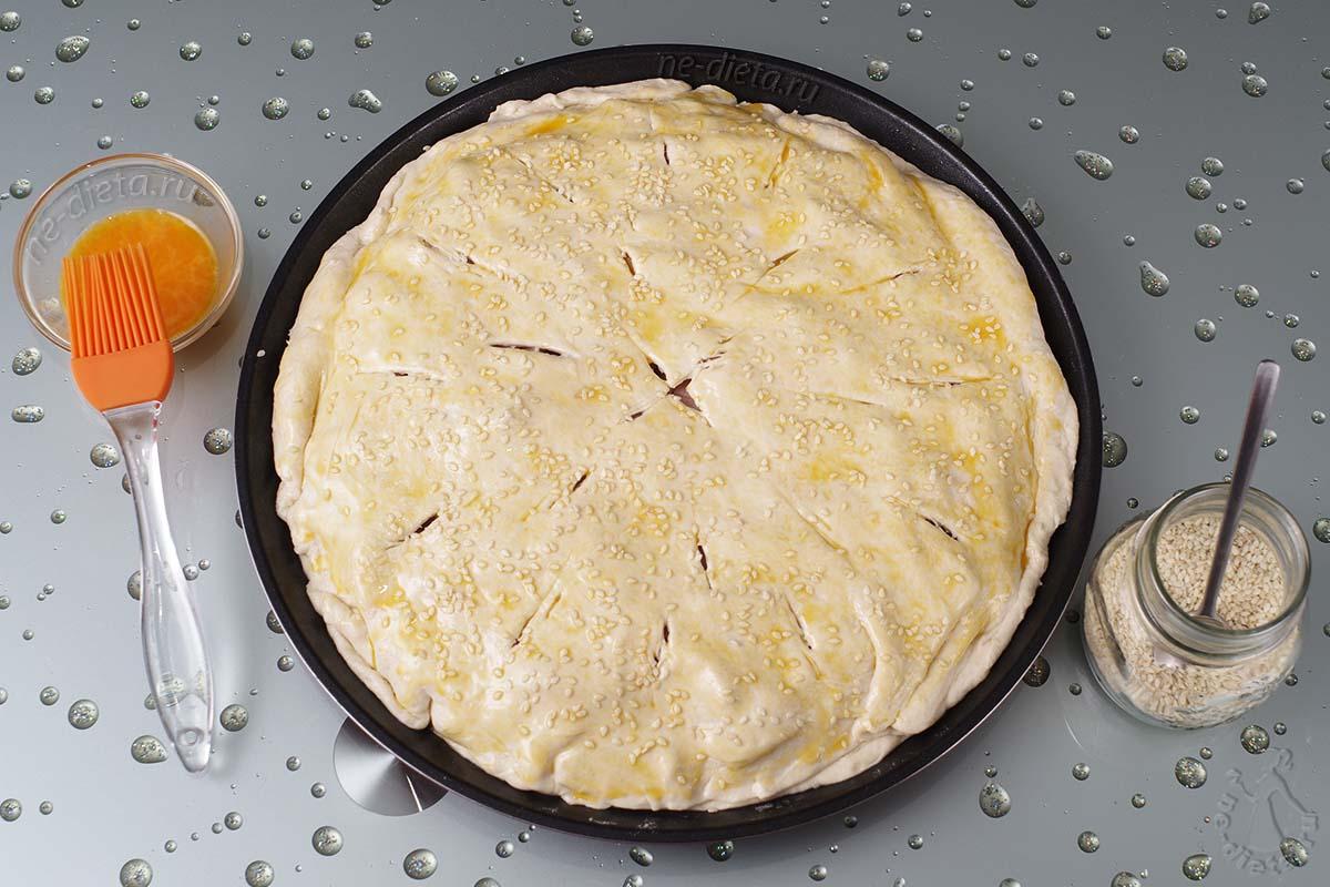 Пирог смазать яйцом и посыпать кунжутом