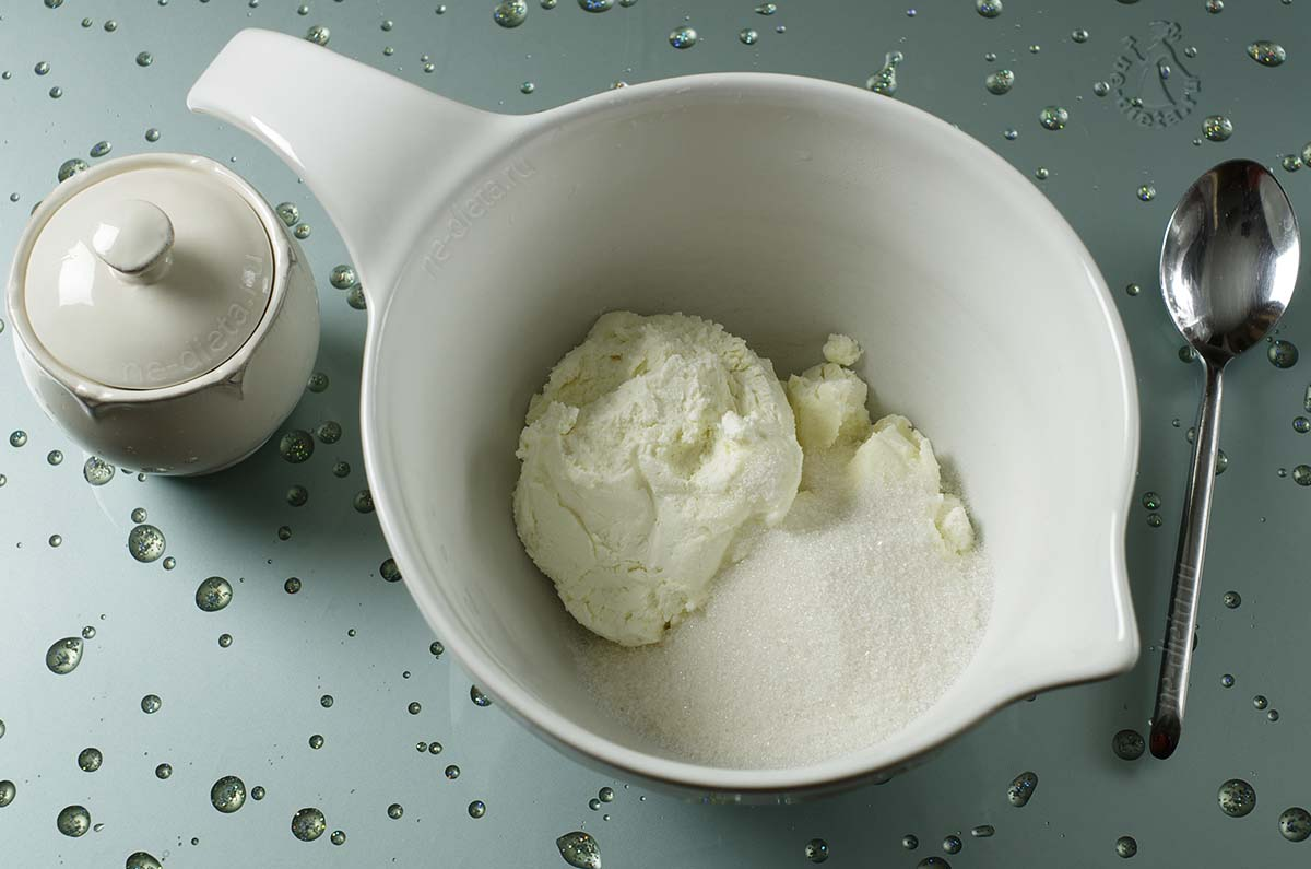 В миску выложить творог и сахар
