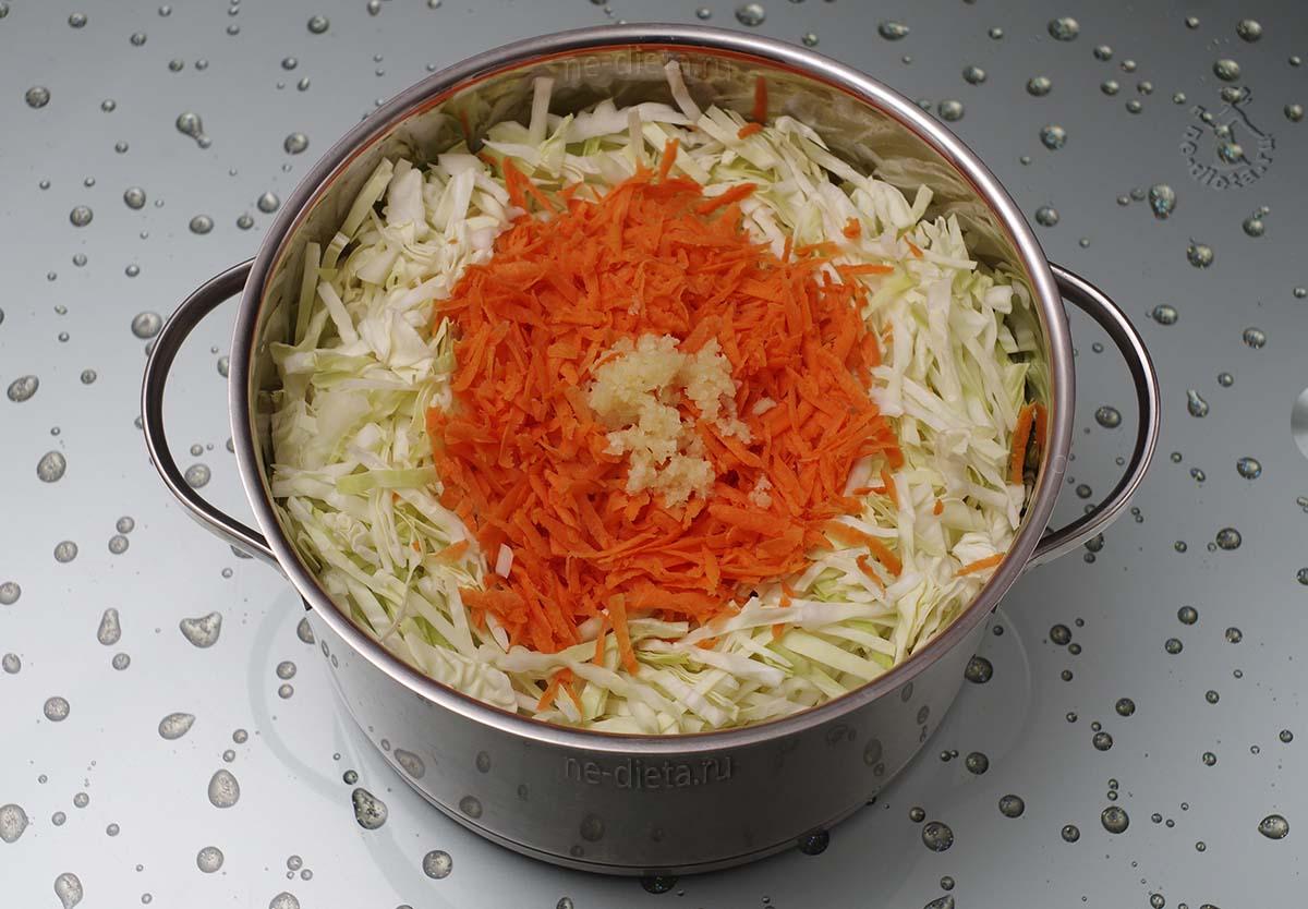 В кастрюлю выложить капусту, морковь и чеснок
