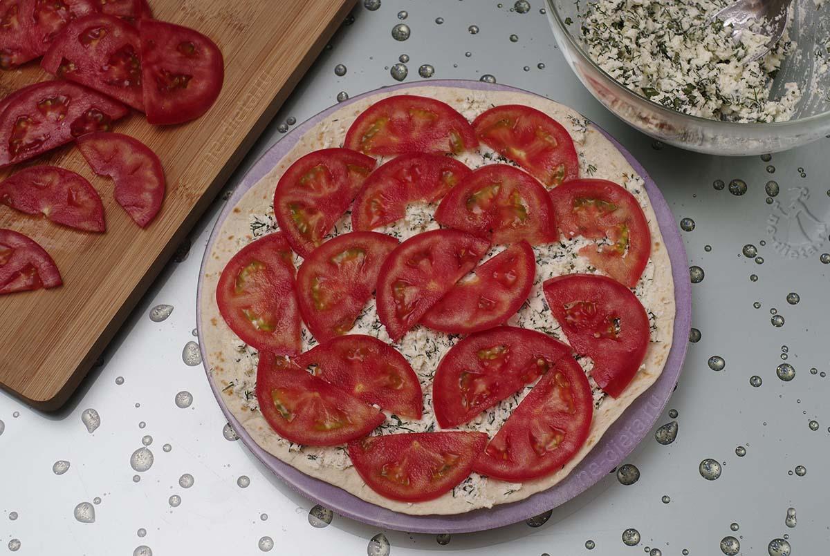 Тортильи намазать пастой из брынзы и выложить помидоры