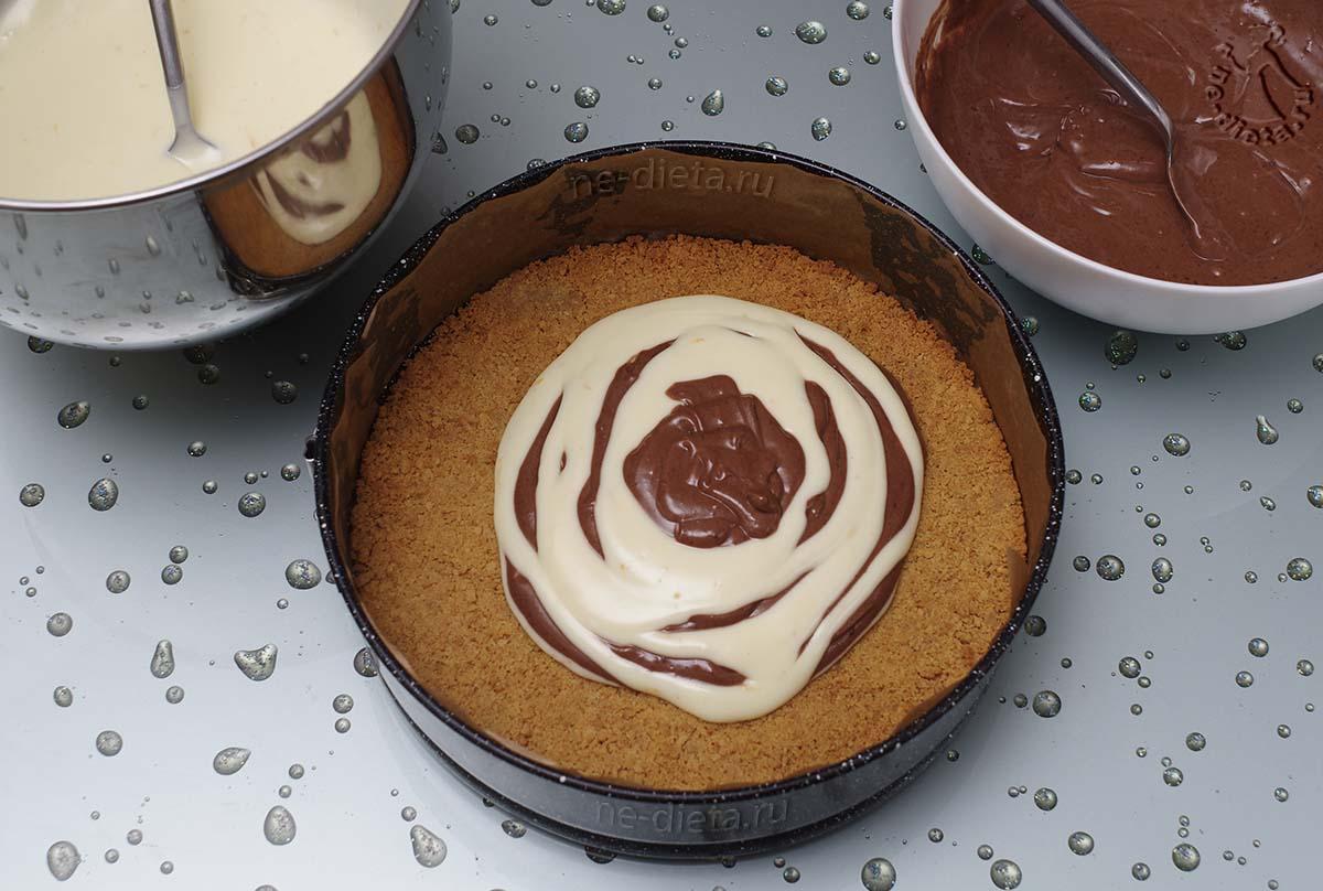 Поочередно вылить белый и шоколадный крем на основу для чизкейка