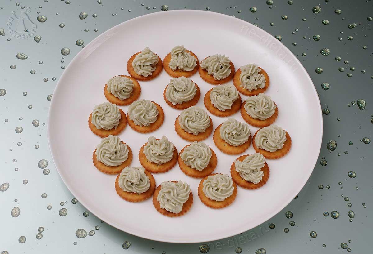 Выложить на крекеры розочки из сыра