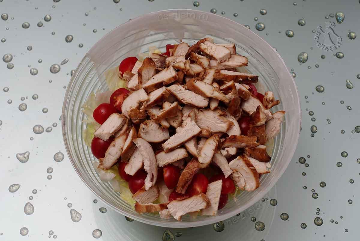 В салатник выложить листья салата, помидоры-черри и куриное филе