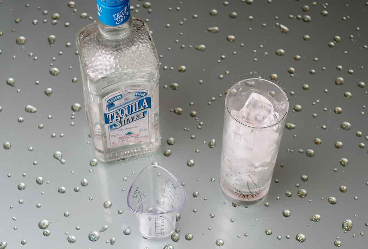 В стакан насыпать лед и налить текилу
