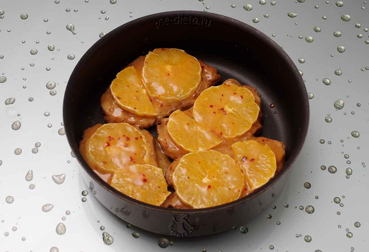 Поверх свинины разложить апельсины и смазать глазурью