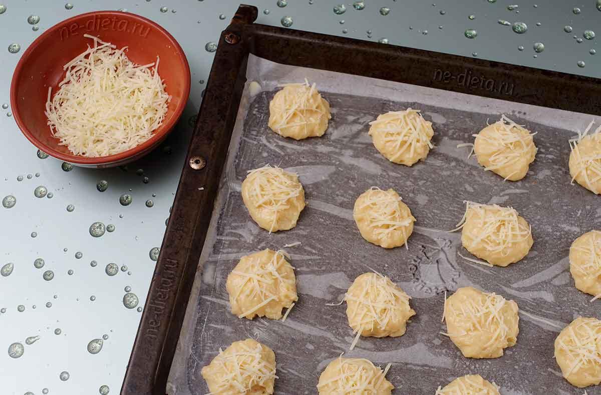 На противень выложить шарики теста и посыпать тертым сыром