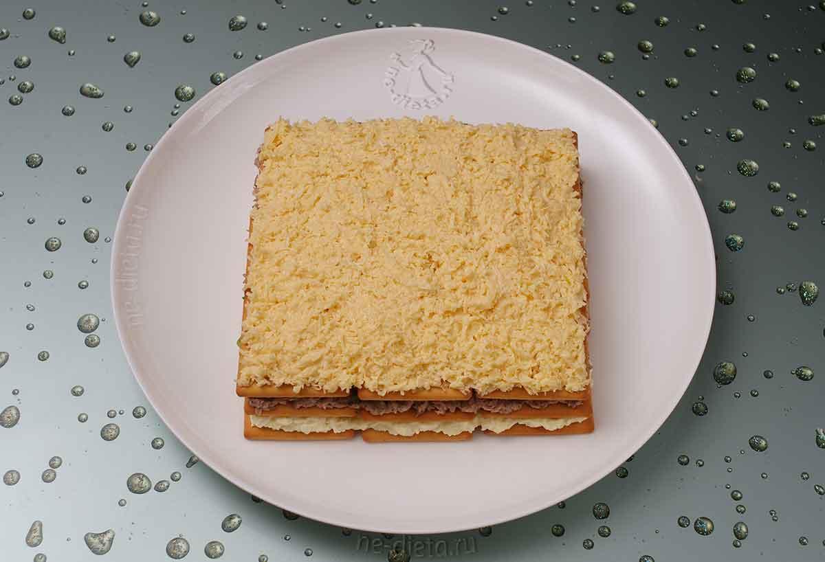 Положить слой крекеров и сыр