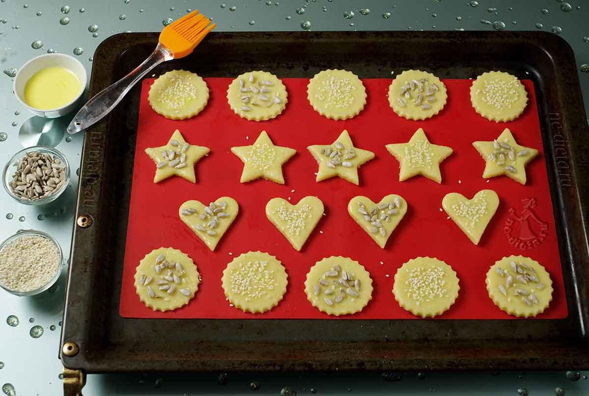Печенье смазать и присыпать семечками и кунжутом