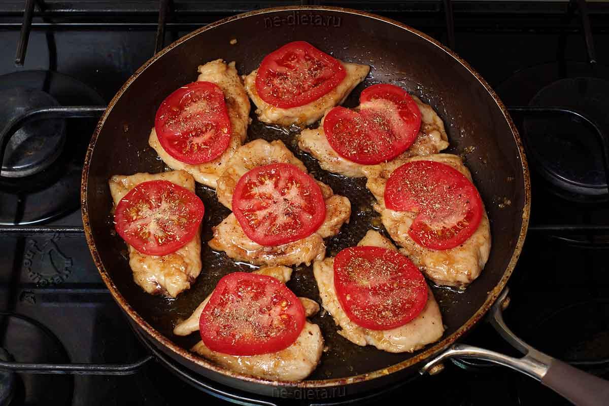 На курицу положить помидор и посыпать сухими травами