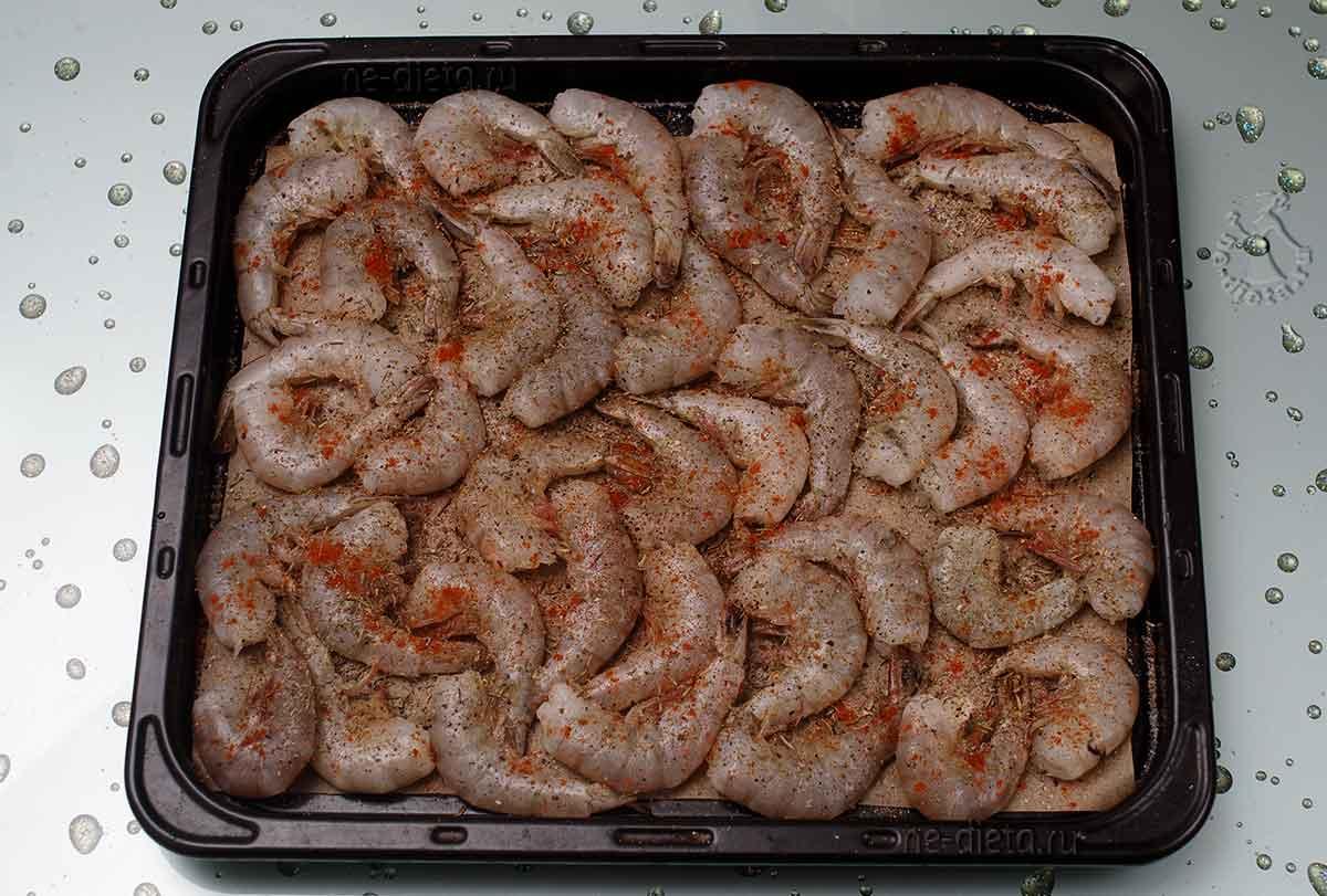 Креветки выложить на противень и посыпать солью и специями