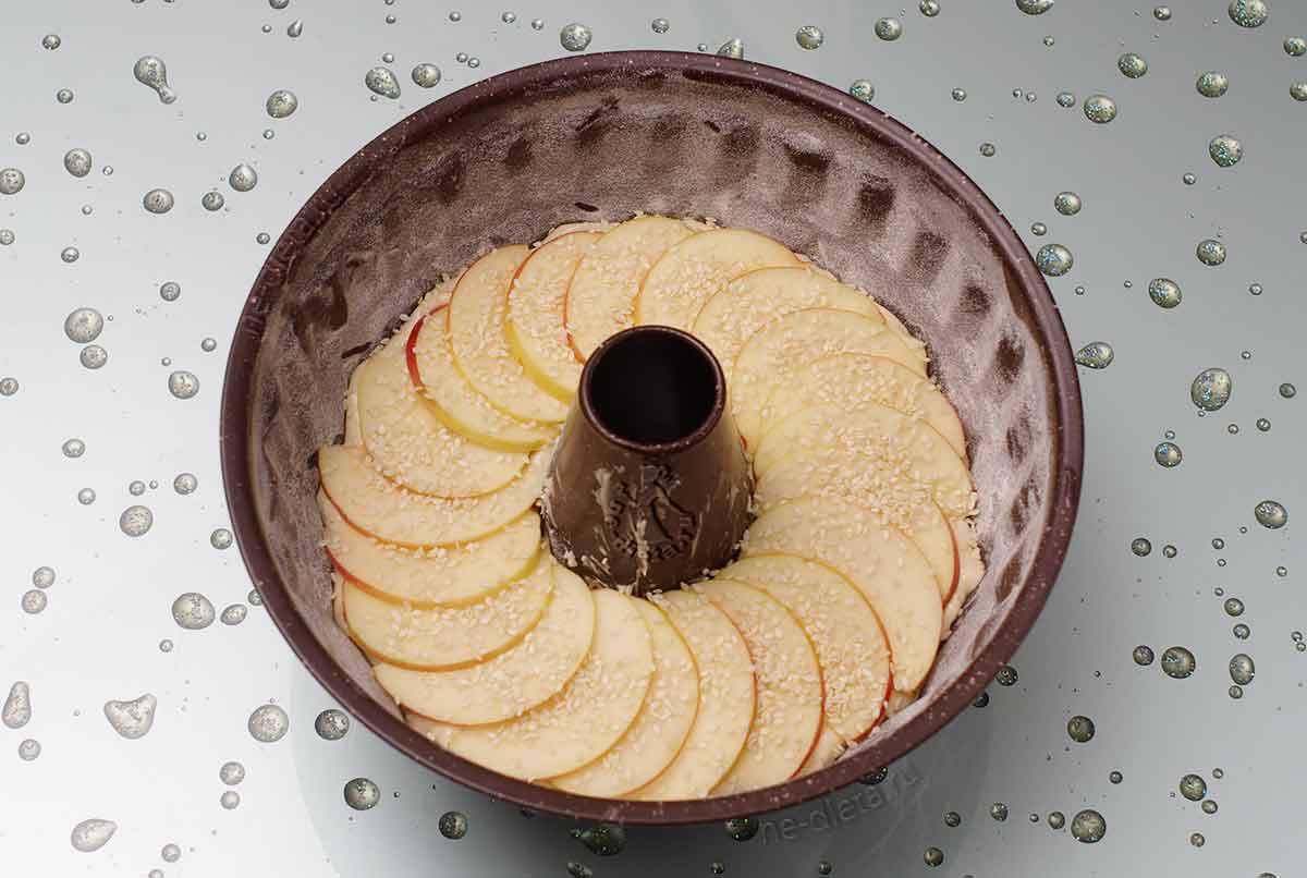 Поверхность кекса украсить яблоками и кунжутом