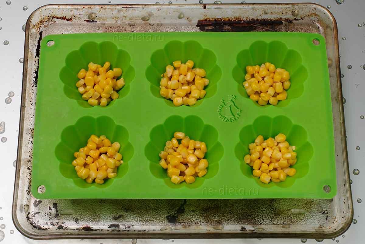 На дно форм выложить оливки и кукурузу