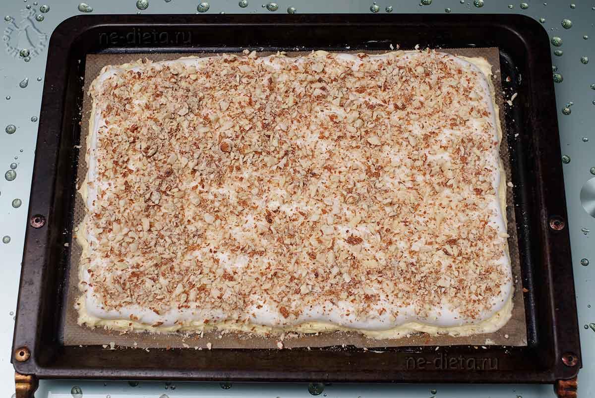 На тесто выложить взбитые белки и молотый миндаль